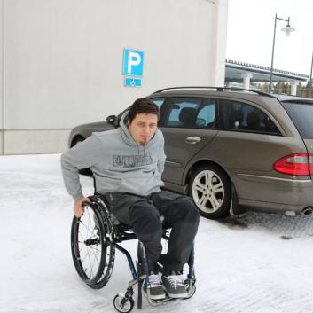Mies pyörätuolissa auto parkkeerattu invapaikalle.
