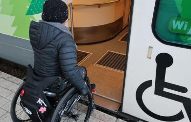 kuvassa pyörätuolia käyttävä henkilö menossa junaan