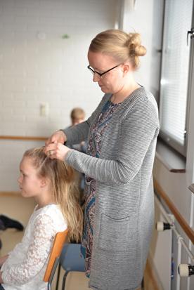 Äiti Krista laittamassa Erinin hiuksia