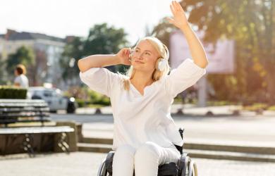 nuori nainen istuu pyörätuolissa ja kuuntelee musiikkia kuulokkeista.